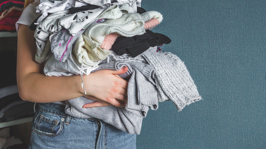 arms filled with used clothes